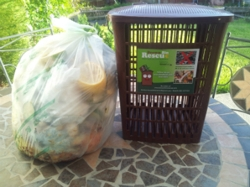 Aerated caddy with compostable bag of food waste beside it.