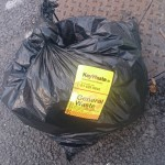 picture of Black rubbish bag with a yellow sticker as a receipt on Dublin's Streets.